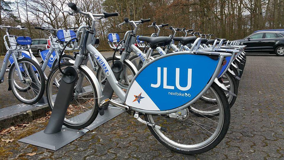 nextbike Leihräder mit Aufschrift JLU und AStA-Logo die an einer Leihstation aufgereiht stehen.