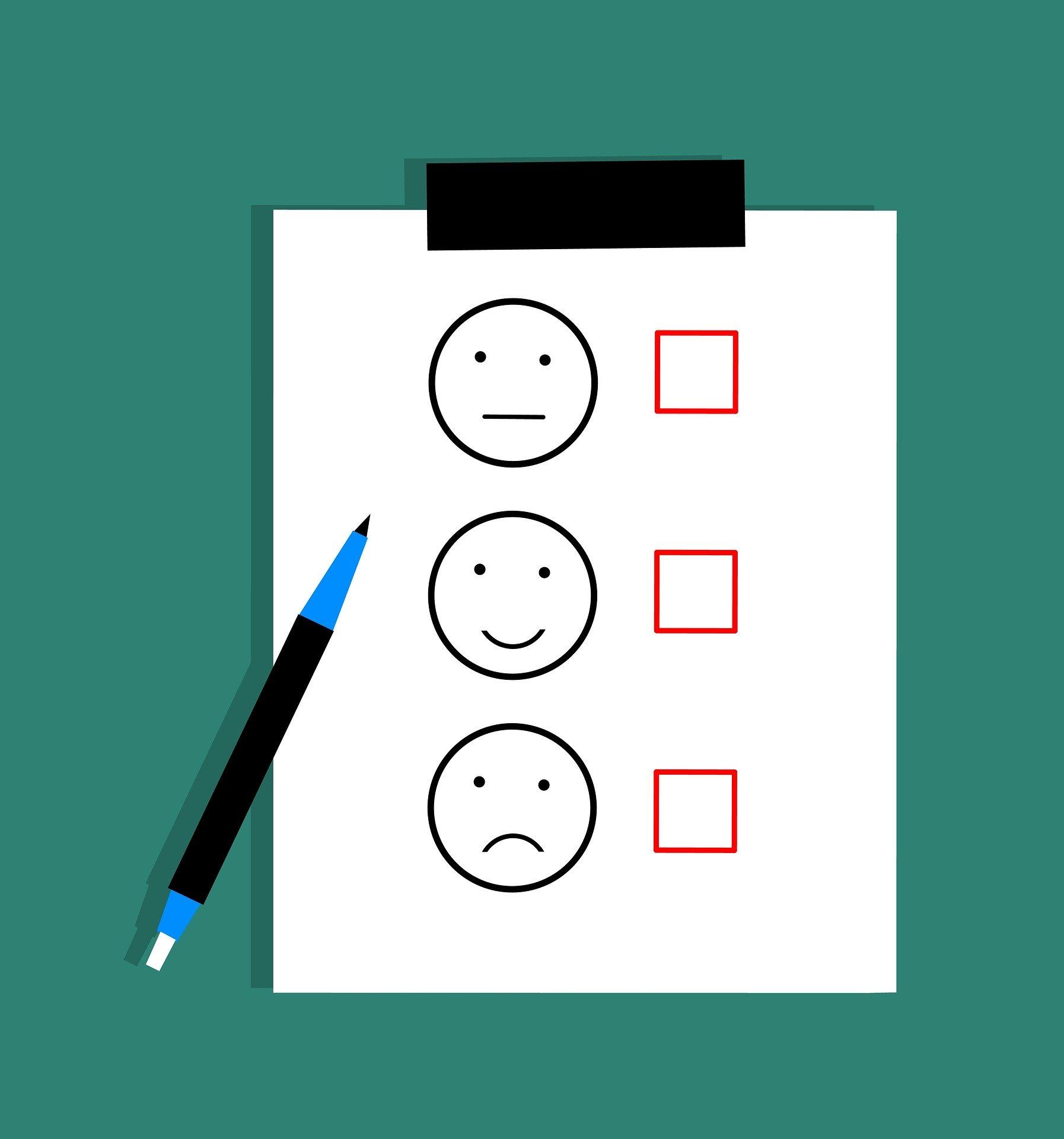 Ein Kuli und ein Klemmbrett sind zu sehen. Auf dem Klemmbrett sind drei Emojis zu sehen: Der obere mit mittelmäßigem Gesichtsausdruck, der mittlere mit zufriedenem und der untere mit unzufriedenem Gesichtsausdruck. Daneben ist jeweils ein Auswahlfeld.