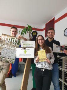 """Arne, Julia und Marvin. Sie halten Plakat """"Stud* et al."""", Recycling-Sammelbox für Handys, Flyer """"Be active - in Gießen"""", eine Zeitung und das Kochbuch """"Studies kochen grün"""""""